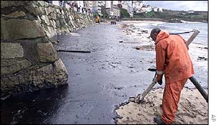 Worker uses special vacuum to clean oil from the beach at Malpica, northern Spain
