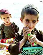 Afghan boys sell sweets by a roadside
