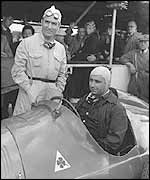 Giuseppe Farina (standing) with Juan Manuel Fangio ahead of the 1950 British Grand Prix