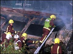 05/10/1999 Firemen climb on the smouldering wreckage of one of the railway carriages