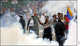 Protesters walk through teargas