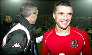 An elated captain Gary Speed shakes hands with manager Mark Hughes following Wales' 2-0 win in Baku
