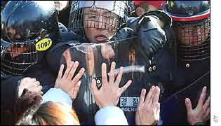 Riot police try to block as South Korean civic group members and students stage an anti-US rally at Camp Casey