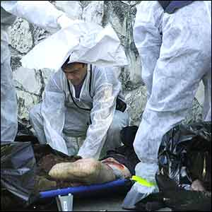 Forensic experts examine the body of a victim
