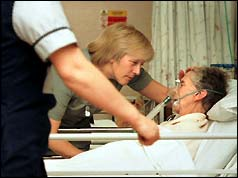 Two nurses at the bedside of an elderly patient