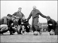 Sir Matt Busby (centre, standing)  with players in 1956