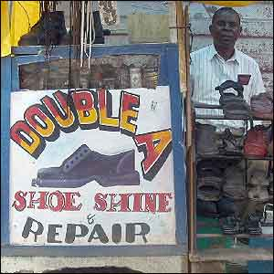 Shoe-shine man, with sign