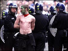 Police officers arrest a protester in Trafalgar Square