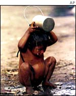 A malnourished child in Delhi tries to cool down.