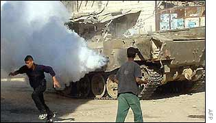 Palestinian youths near Israeli tank in  Jenin