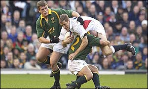 Will Greenwood of England is tackled by James Dalton and Deon Carstens