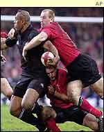 Wales wing Gareth Thomas halts the charge of New Zealand's Jonah Lomu