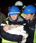 Two armed forces firefighters cradle a baby rescued from flats in Southampton