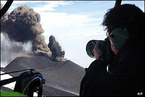 A photographer takes an aerial picture of the smoke rising from Mount Etna