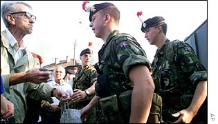 Serb man holding a rock is confronted by British soldiers
