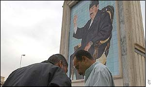Iraqi men stand underneath a portrait of Saddam Hussein in Baghdad