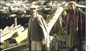 Quake victims outside ruined house