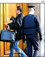 Plainclothes policeman carrying a bundle of documents