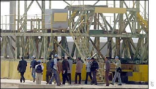 Weapons inspectors examine a metal structure in Iraq