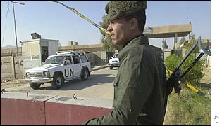An Iraqi soldier watches UN vehicles as they make their way into the factory
