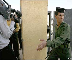 An Iraqi soldier prevents journalists from following the inspectors