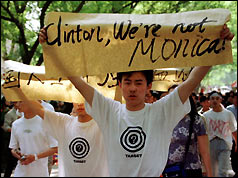 "A chinese student holds up a placard aimed at President Clinton - ""Clinton, we're not Monica"""