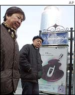 Couple walk past Motorola billboard in Beijing