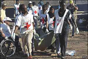 Red Cross workers carry away one of the victims