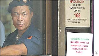 A building security detail mans his post by the door leading to the Canadian Embassy at Makati city, east of Manila
