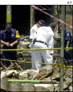 Police search through the remains of the Safari Club in Bali