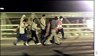 Asylum seekers making for the entrance to the Channel Tunnel