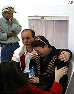 Miki Anter, aunt of slain brothers, mourns with her husband