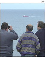 Men look out to sea in search of the huge oil slick heading for the Spanish coast