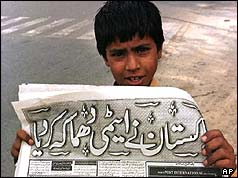 A young newspaper vendor holds up the evening paper - 28 May 1998