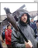 A protester marches with a crucified bird covered in oil