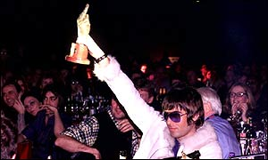 Liam Gallagher holds up an award during the 2001 NME Carling Awards