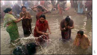 People bathe at the confluence of Ganges, Jamuna and Saraswati rivers during Kumbh Mela