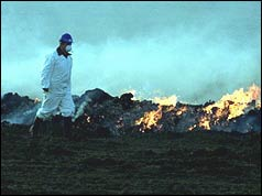 Farmer dressed in protective clothing surveying burning pyre