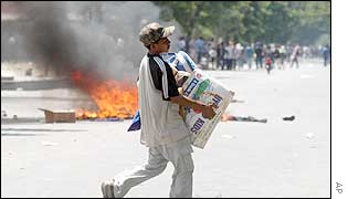 An East Timorese carries goods looted from shops in Dili, East Timor, 4 Dec. 2002.