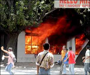 East Timorese run after setting fire on a foreign-owned supermarket in Dili, East Timor, 4 Dec. 2002 (AP photo)