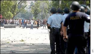 East Timorese civilian police officers block a protesters on a road in Dili, East Timor, 4 Dec 2002.