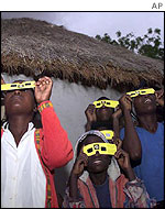 Villagers watching the eclipse through special glasses