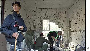 Palestinians examine the damage after several missiles hit a building in Gaza