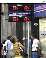 A woman looks at a currency exchange sign in Buenos Aires