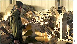 Iraqi soldier looks at disabled anti-aircraft battery at the Muthanna plant