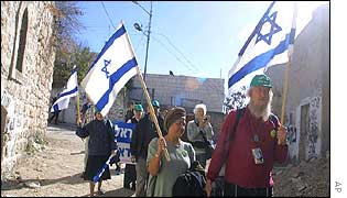 Israeli settlers walk through Hebron, a town in the West Bank