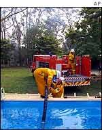 Firemen pump water from a swimming pool at Glenorie