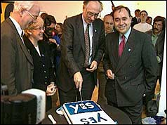 Donald Dewar cuts a cake to celebrate the 'Yes' vote for political referendum
