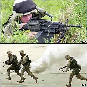 A marine aims with a machine gun, more run past smoke