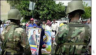 Soldiers look on as a street vendor holds pictures of President Hugo Chavez